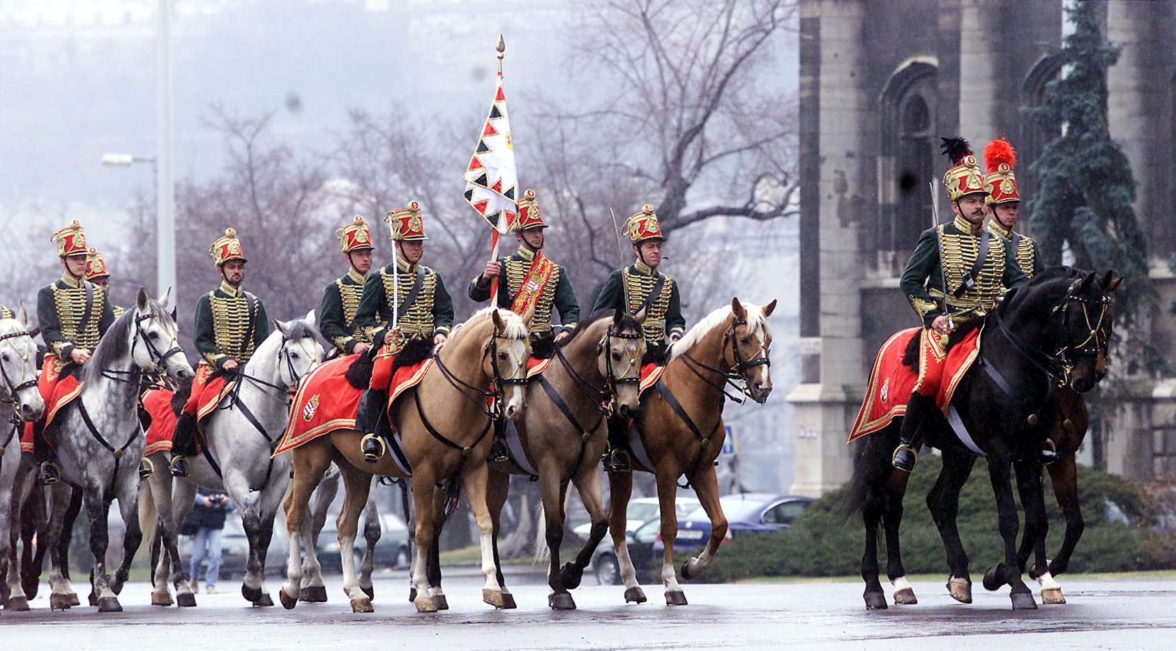 Budapest, 2001. 03. 13. Negyvenhét évi várakozás után ismét van Magyarországnak olyan huszáralakulata, amely nemzeti ünnepeinken, vagy állam- és kormányfők fogadása alkalmából méltóképp képviseli történelmi államiságunk megjelenítését. A magyar huszárság hagyományait híven követő lovas díszegység felállításának és kiképzésének költségeit a Belügyminisztérium fedezte. Tagjait elsősorban a lovasrendőrség állományából toborozták. A képen: a Magyar Köztársaság Nemzeti Lovas Díszegysége a március 15-i nemzeti ünnepünkön mutakozik be először, az ünnepség főpróbáját március 13-án tartották a Parlament előtt. MTI Fotó: Illyés Tibor