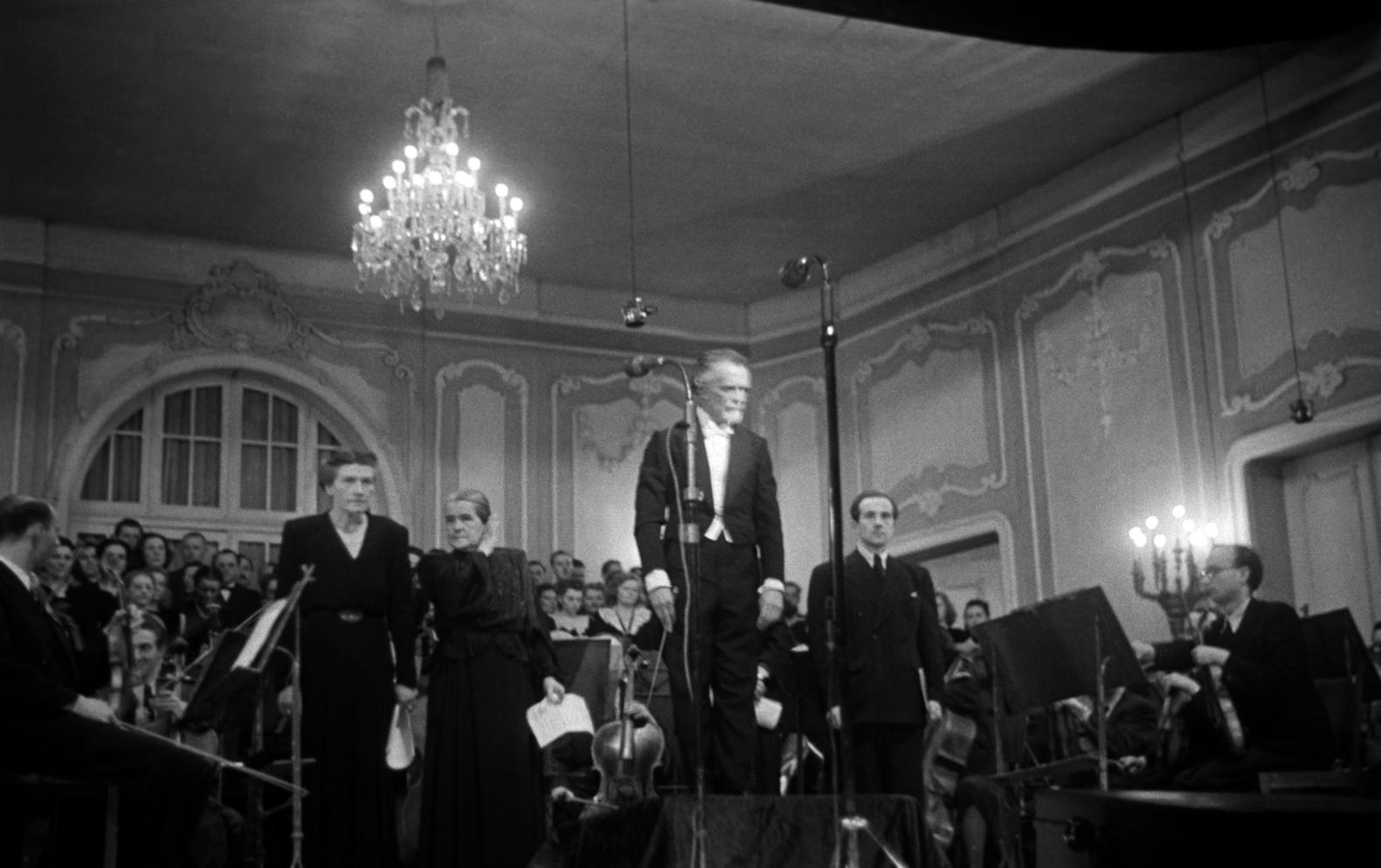 Budapest, 1946. március 15. Kodály Zoltán zeneszerző (j2, áll), Báthy Anna operaénekesnő (szoprán) (b1, áll), Basilides Mária operaénekesnő (alt) (b2, áll) és Rissay Pál operaénekes (basszus) (j1, áll) a tapsot fogadják. Kodály Zoltán: Budavári Te Deumja hangzott el a Székesfővárosi Zenekar és a BHTV Liszt Ferenc Énekkar előadásában, a szerző vezényletével a Nemzeti Bizottság március 15-i ünnepségének díszelőadásán a Nemzeti Színházban. MTI Fotó/MAFIRT: -
