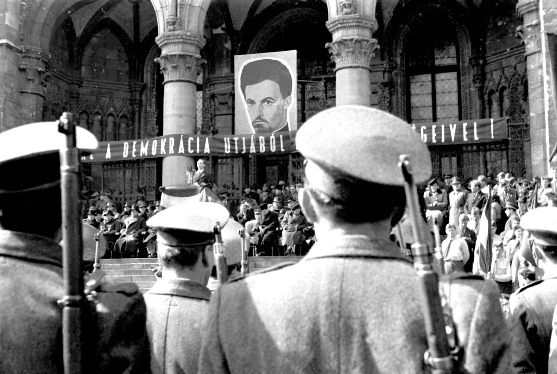 Budapest, 1947. március 15. Rajk László belügyminiszter beszédét hallgatják a résztvevők a Parlament előtt a Kossuth téren, a március 15-i ünnepi gyűlésen Petőfi Sándor portréja alatt. MTI Fotó/MAFIRT: Adorján Rezső