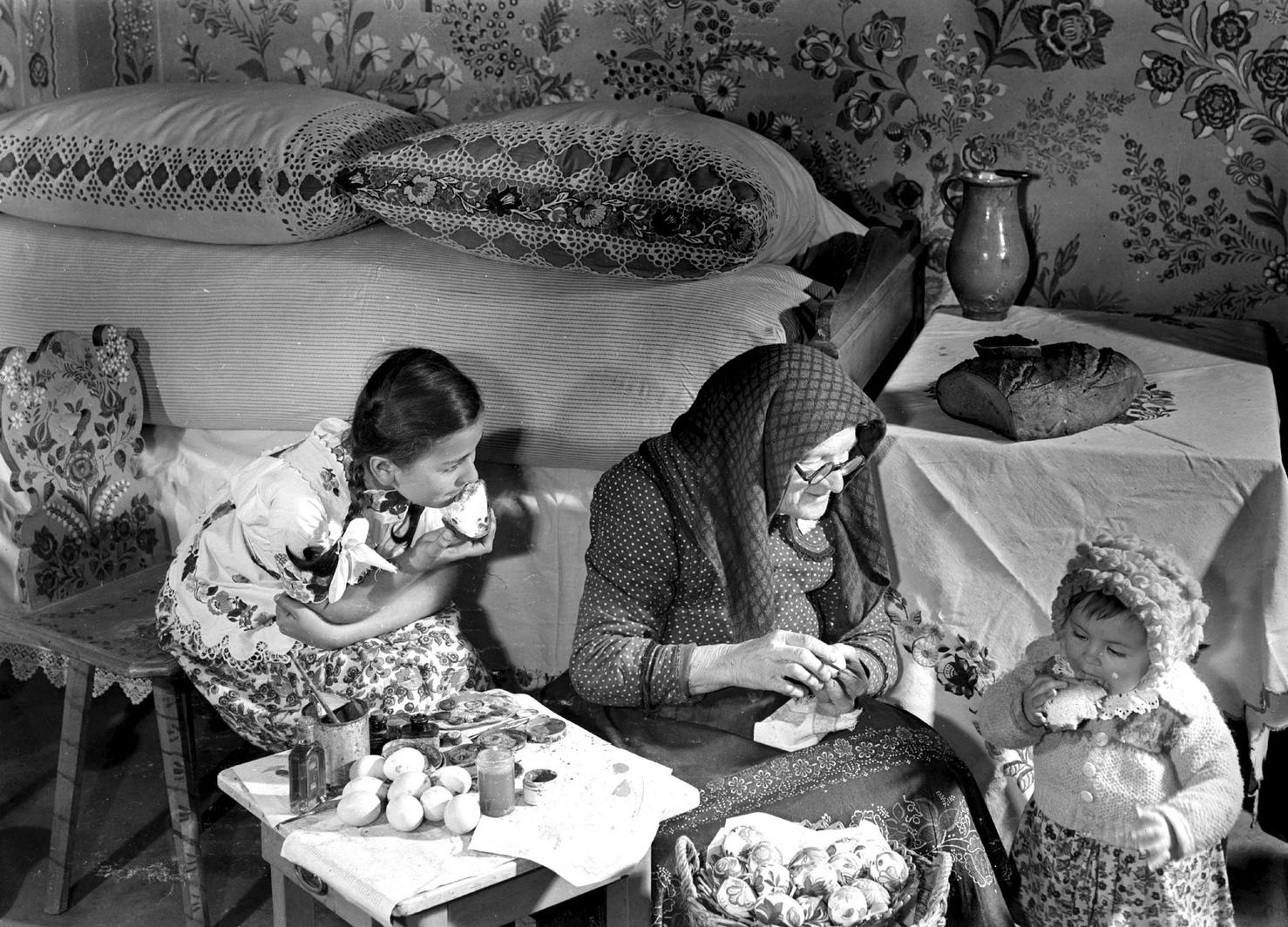 Öregcsertő, 1954. április 12. A húsvéti ünnepek közeledtével festi a tojásokat özvegy Tamásné Rigó Borbála (vacsorás Boris néni) unokájával és dédunokájával. Magyar Fotó