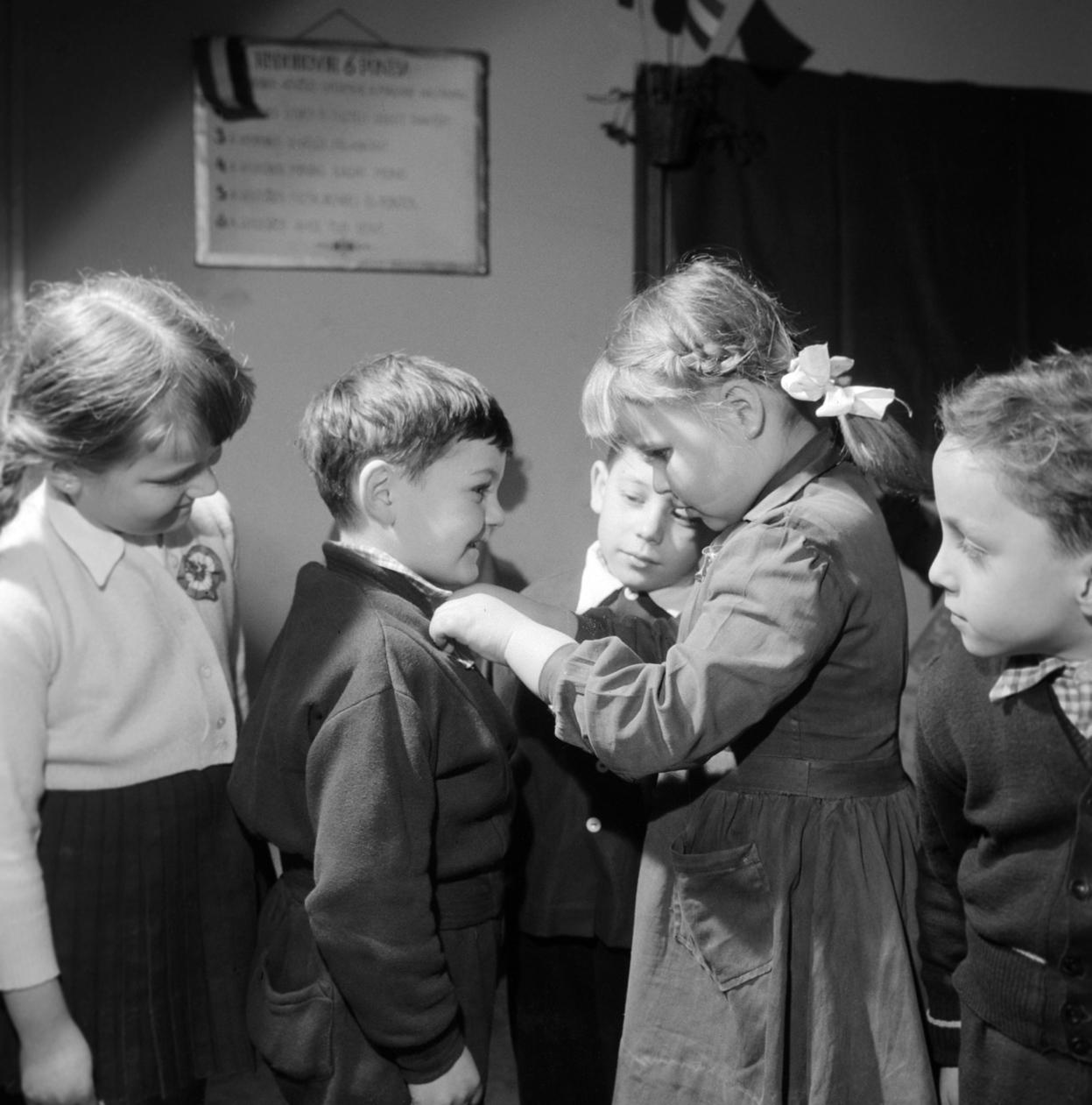 Budapest, 1960. március 14. Botos Ági diák segít a pajtásainak kitűzni a kokárdáikat a Lisznyai utcai általános iskola Március 15-i ünnepségén. MTI Fotó: Patkó Klári