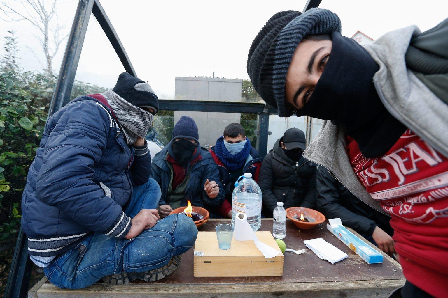 Zeebrugge, 2016. február 3. Nagy-Britanniába tartó migráns férfiak sállal védik az arcukat a hidegtől, mialatt gyertyaláng mellett próbálnak melegedni a nyugat-belgiumi Zeebrugge kikötőváros egyik buszmegállójában 2016. február 3-án. (MTI/EPA/Laurent Dubrule)