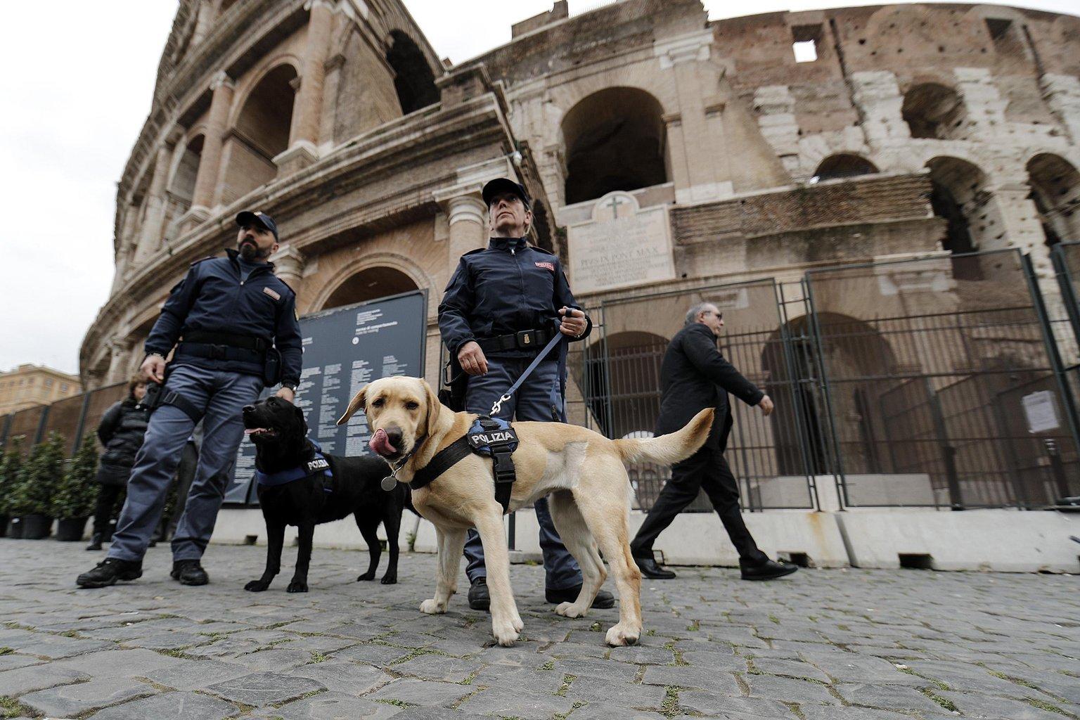 Kutyás rendőrök bombát keresnek a római Colosseumnál, mielőtt Ferenc pápa végigjárja a nagypénteki keresztutat, a Via Crucist 2018. március 30-án. Mintegy tízezer rendőr biztosítja a Colosseum környékét a keresztút idején, amelynek évszázadokra visszatekintő hagyománya során Jézus szenvedéstörténetének 14 állomását elevenítik fel a katolikusok. (MTI/EPA/Riccardo Antimiani)