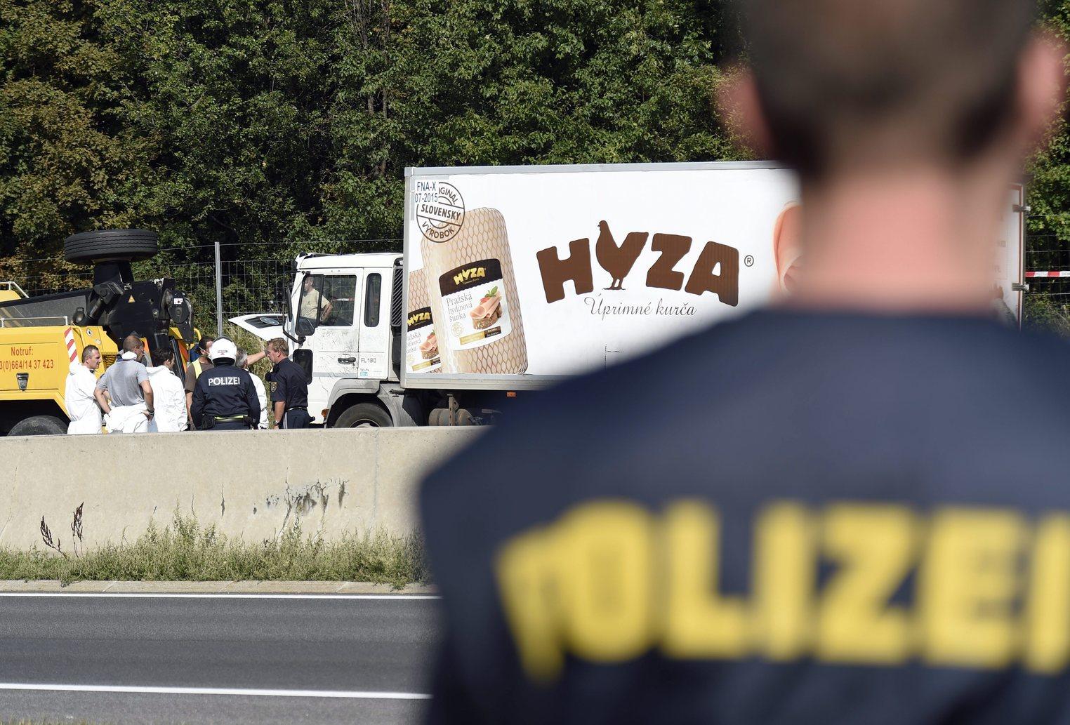 Védőruhába öltözött helyszínelők vizsgálnak egy teherautót az A4-es autópályán Pandorf közelében 2015. augusztus 27-én. A járműben hetvenegy menekült holttestére bukkantak a hatóságok. (MTI/EPA/Herbert P. Oczeret)