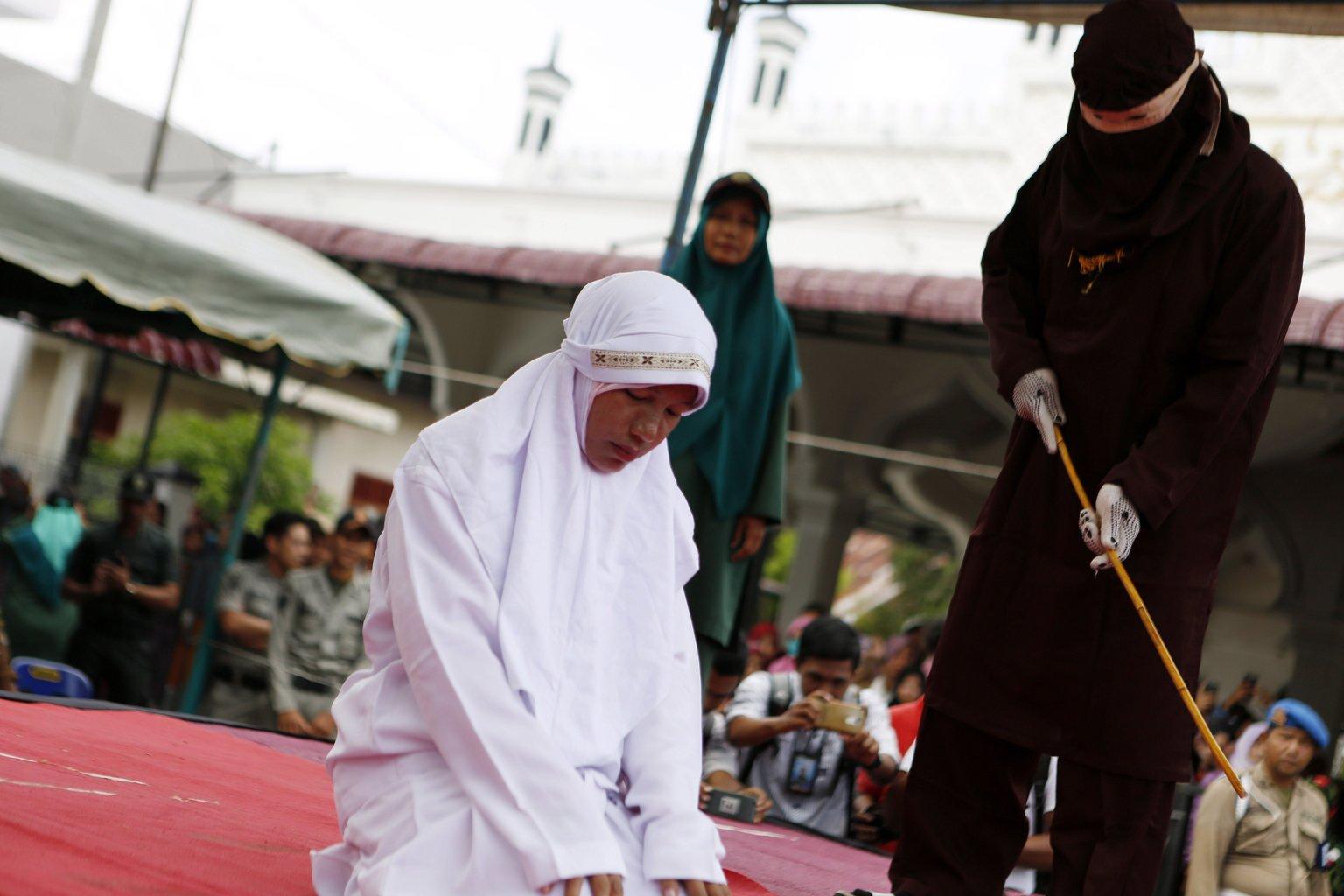 Az iszlám vallási törvénykezés, a saría ellen vétő nőt botoznak meg nyilvánosan az indonéziai Aceh tartomány székhelyén, Banda Acehben 2017. március 20-án: a nőt 25 botütésre ítélték házasságon kívüli nemi kapcsolat miatt – a botozás az Aceh tartományban alkalmazott saría egyik büntetési formája (Fotó: MTI/EPA/Hotli Simanjuntak)