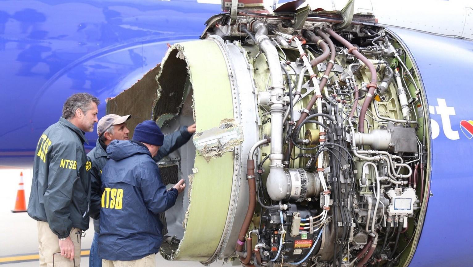 Szakértők vizsgálják a Southwest Airlines 1380-as járatának felrobbant hajtóművét a Philadelphiai Repülőtéren 2018. április 17-én, miután a gép kényszerleszállást hajtott végre – a New Yorkból a dallasi Love Fieldbe tartó járat hajtóműve repülés közben robbant fel, a gép ablakai betörtek, a balesetben legkevesebb egy ember életét vesztette (Fotó: MTI/EPA/NTSB)