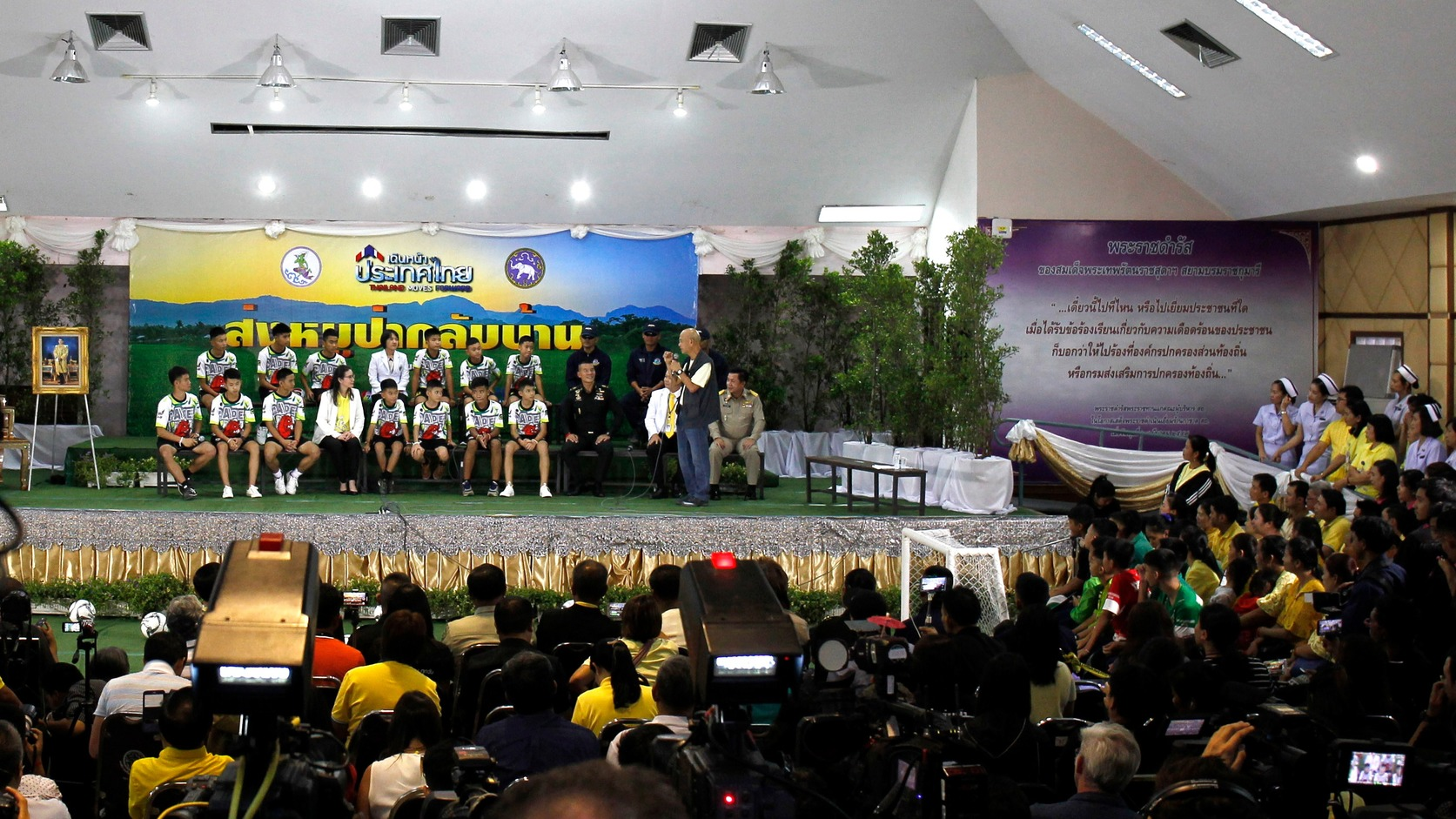 epa06896597 Thirteen rescued members of Wild Boar soccer team are surrounded by government officials, soldiers and journalists during the military governmental TV pool broadcasting program at Chiang Rai Provincial Administrative Organization in Chiang Rai province, Thailand, 18 July 2018. The thirteen members of Wild Boar child soccer team, including their assistant coach, who were trapped in the Tham Luang cave since 23 June 2018, made their first appearance on the day for a tightly-controlled interview with the media after they were rescued, before returning to their homes with families.  EPA/PONGMANAT TASIRI