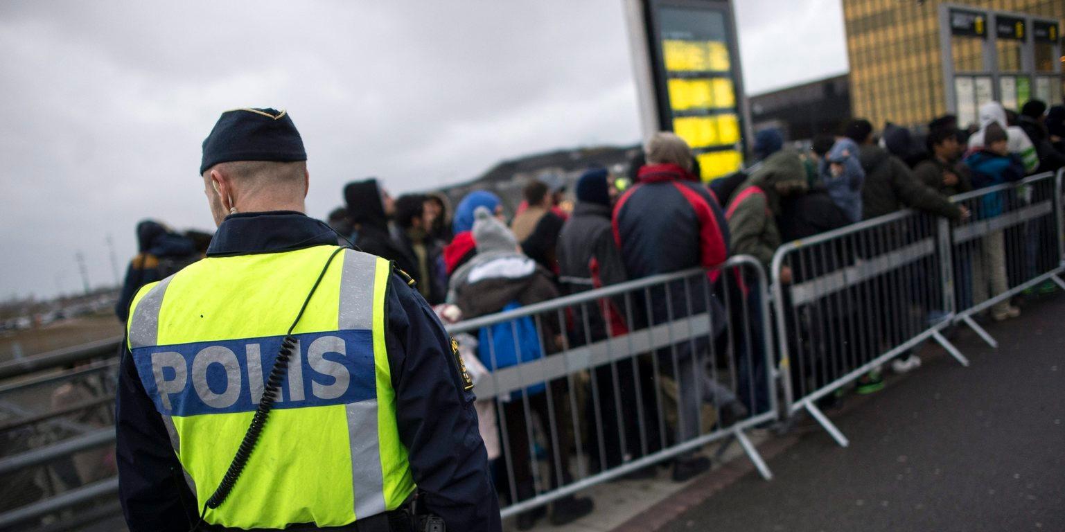 A 2016. január 28-án közreadott képen egy svéd rendőr felügyeli az újonnan érkezett menedékkérők vonulását a malmöi Hyllie pályaudvar előtt (Fotó: MTI/EPA/TT/Johan Nilsson)