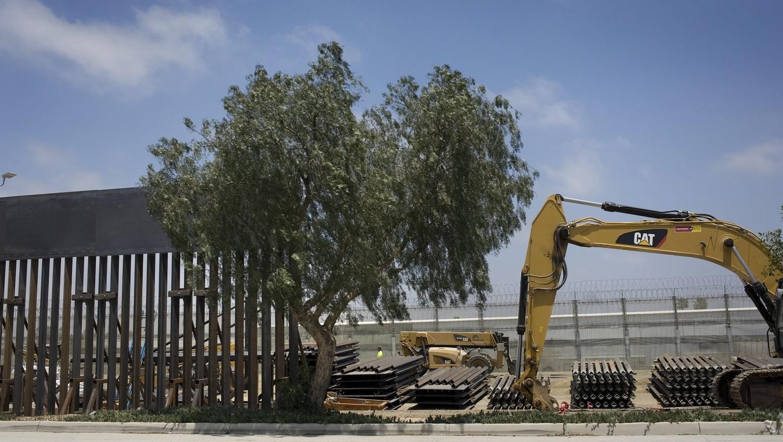A mexikói-amerikai határ mexikói oldaláról készített felvétel: munkások dolgoznak a két országot a mexikói Tijuana és az egyesült államokbeli San Diego térségében elválasztó határkerítésnél 2018. június 20-án – a munkálatok során az elsődleges, régi határkerítést egy magasabb és nagyobb védelmet nyújtó fémkerítésre cserélik ezen a szakaszon (MTI/EPA/David Maung)