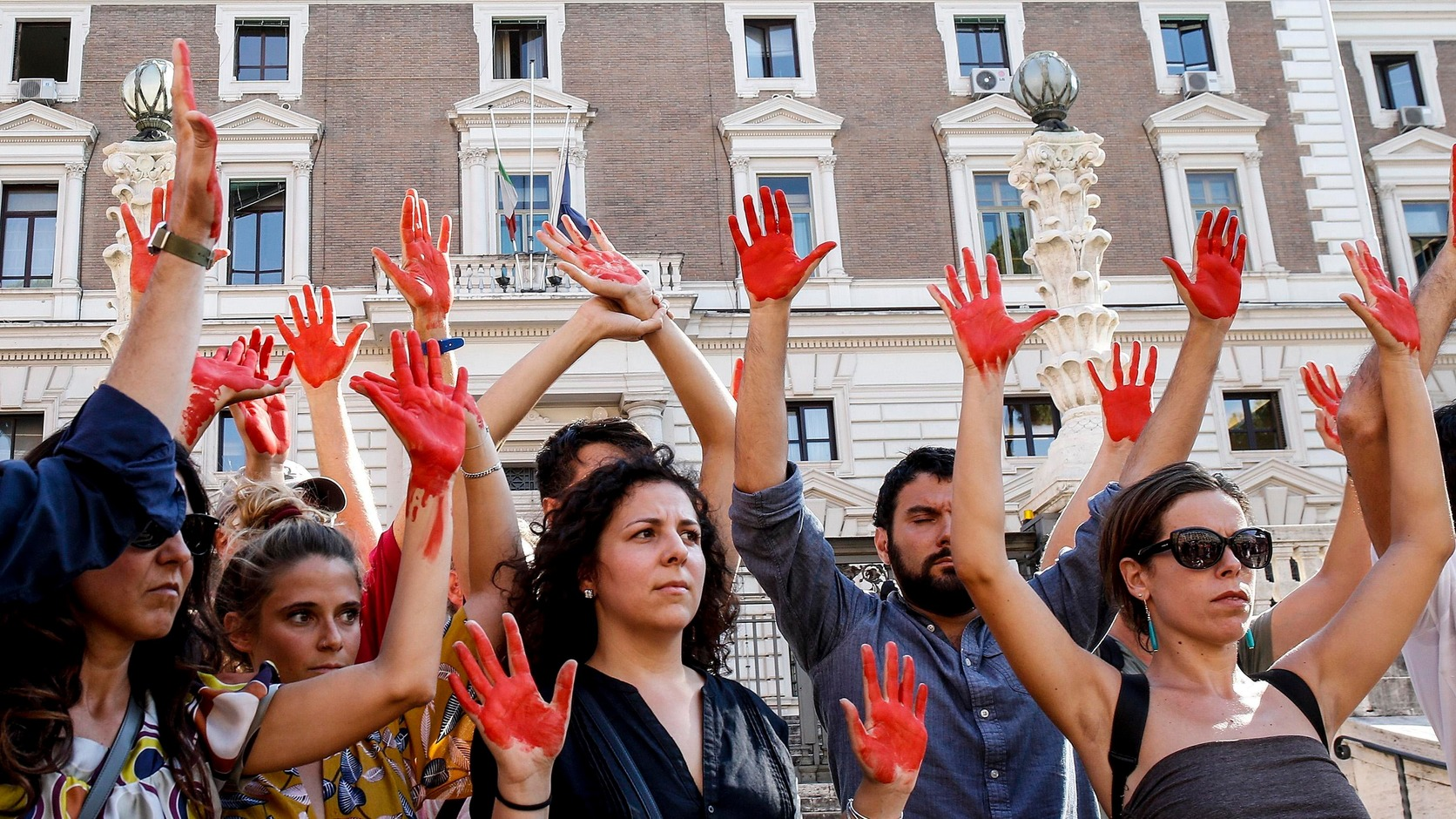 Róma, 2018. július 18. Az olasz Radikális Párt (PR) támogatói pirosra festett tenyérrel tüntetnek a Matteo Salvini olasz belügyminiszter által képviselt politikai irányvonal ellen a belügyminisztérium székháza előtt Rómában 2018. július 18-án. (MTI/EPA/Fabio Frustaci)