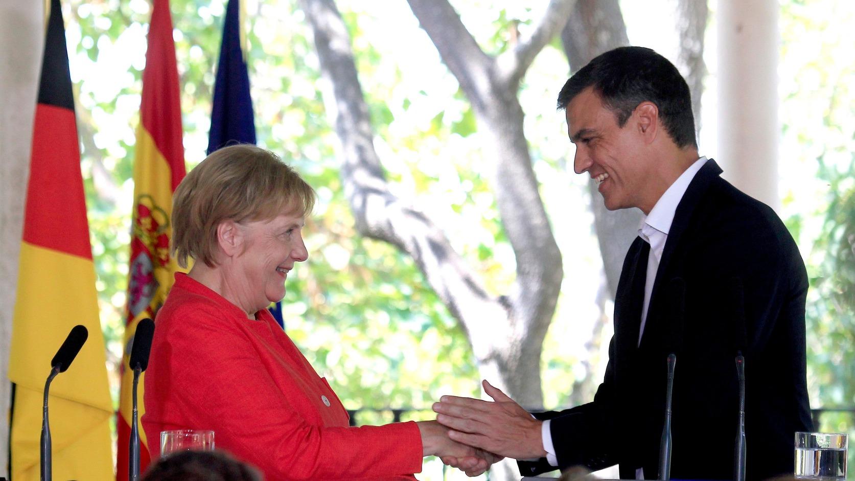 Sanlúcar de Barrameda, augusztus 11. Pedro Sánchez spanyol miniszterelnök (j) és Angela Merkel német kancellár kezet fog sajtóértekezletük kezdetén a dél-spanyolországi Sanlúcar de Barrameda településen 2018. augusztus 11-én. (MTI/EPA/A. Carrasco Ragel)