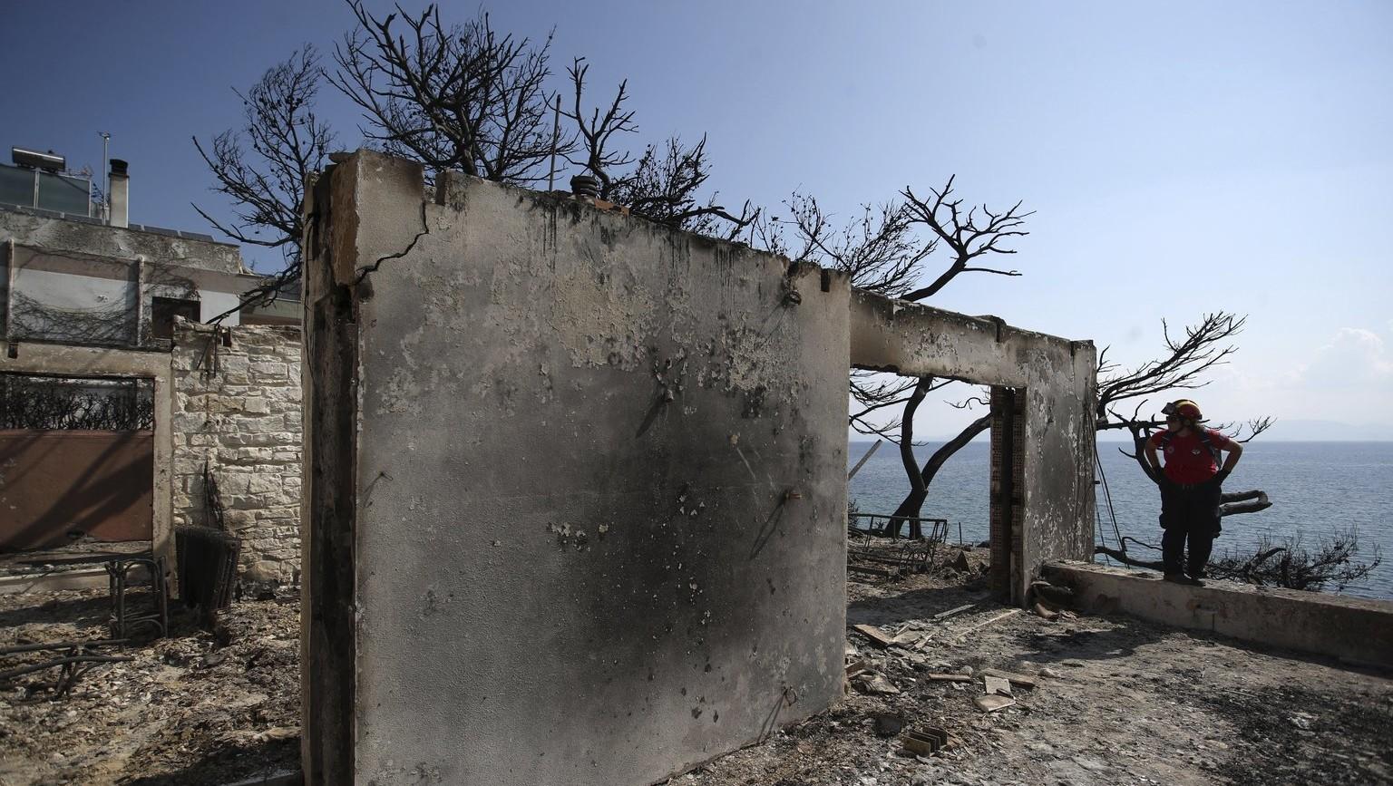 Eltűnt személyek után kutat a Görög Vöröskereszt munkatársa egy leégett lakóépületben, az Athéntól keletre fekvő, tűzvész sújtotta Matiban 2018. július 25-én (Fotó: MTI/AP/Thanászisz Sztavrakisz)