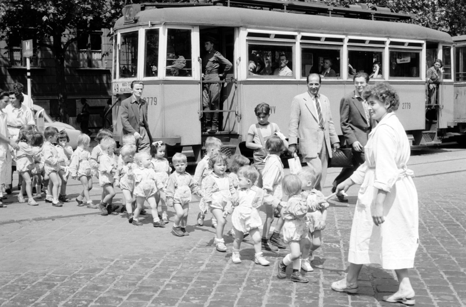 Budapest, 1957. augusztus 7. Kötélbe kapaszkodnak az óvodások, úgy kelnek át az úttesten gondozónőik kíséretében a 49-es villamos megállójában. MTI Fotó: Fényes Tamás