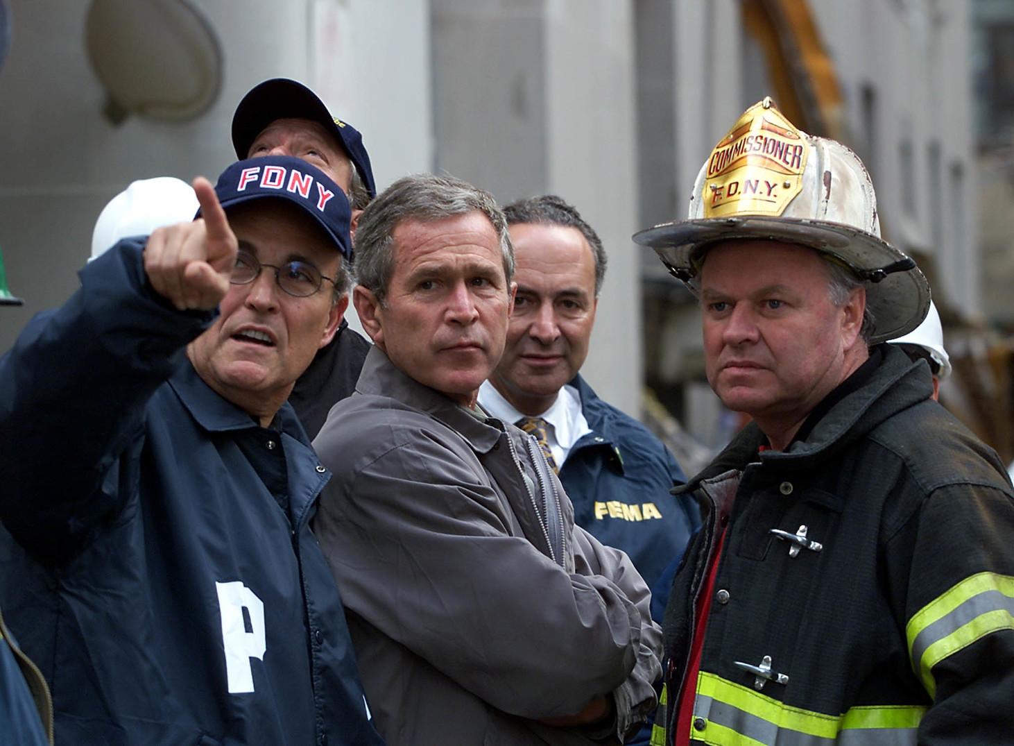 George W. BUSH amerikai elnök (k) Rudi GIULIANI New York-i polgármester (b) kíséretében megtekinti a New York-i Világkereskedelmi Központ eső áztatta romjait, a deformálódott acélszerkezetek között 2001. szeptember 14-én. Három nappal korábban két eltérített utasszállító repülőgép nekihajtott a központ 110 emeletes ikertornyainak, amelyek röviddel később összedőltek. (MTI/EPA/AFP/Paul Richards)