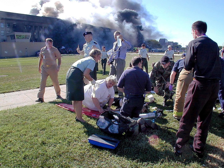 Washington, 2011. szeptember 6. 2001. szeptember 11-i kép, amelyen sebesülteket látnak el az amerikai védelmi minisztérium sűrű füstel égő washingtoni épülete előtt, miután egy terroristák által eltérített utasszállító repülőgép nekihajtott a Pentagonnak. Ezen a napon két eltérített gép ugyancsak belerepült a New York-i Világkereskedelmi Központ 110 emeletes ikertornyai felső szintjeibe, és bomba robbant a washingtoni külügyminisztériumnál is. (MTI/EPA/Amerikai haditengerészet/Mark D. Faram)