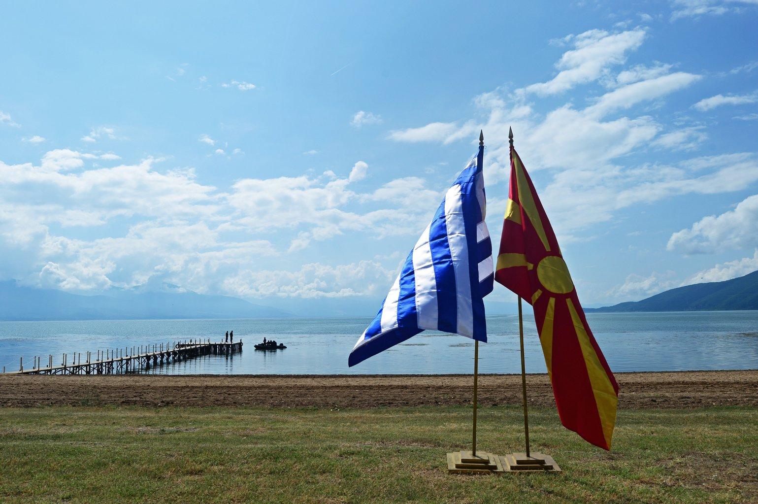 A görög (b) és a macedón zászló a Preszpa-tó partján, a macedóniai Oteszovo közelében 2018. június 17-én. A macedón és a görög külügyminiszter aláírta a Macedónia nevéről a két ország között kialakult vitát lezáró egyezményt a görög-macedón-albán hármas határ térségében, a Preszpa-tó görög oldalán fekvő Pszaradesz faluban 2018. június 17-én. (MTI/EPA/Nake Batev)