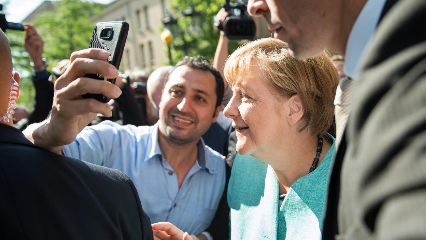 Berlin, 2015. szeptember 10. Angela Merkel német kancellárral (k) készít közös felvételt egy menekült a német szövetségi bevándorlás- és menekültügyi hatóság egyik berlini befogadó állomásán 2015. szeptember 10-én. (MTI/EPA/Bernd von Jutrczenka)