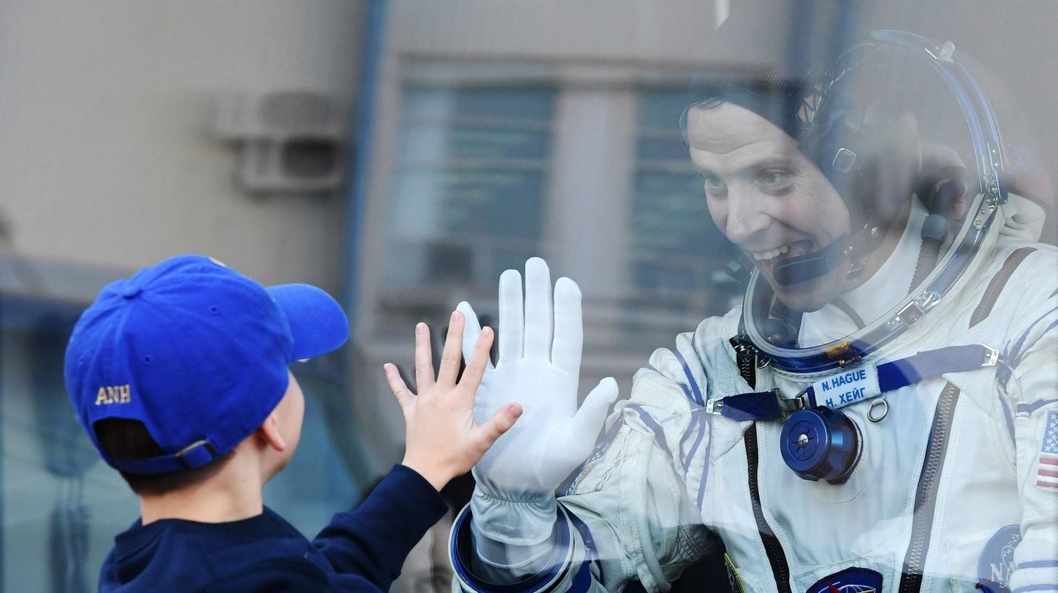 Nick Hague, amerikai űrhajós egy kisgyerektől búcsúzik a Szojuz MSz-10-es űrhajó startja előtt a kazahsztáni Bajkonur orosz űrközpontban 2018. október 11-én (Fotó: MTI/EPApool/Kirill Kudrjavcev)