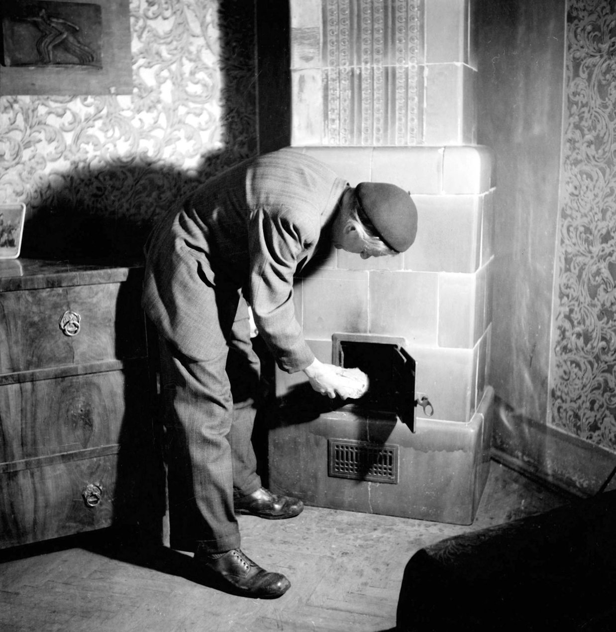 Budapest, 1946. február 27. Bokros Birman Dezső (1889-1965) szobrászművész otthonában fát tesz a cserépkályhájába. MTI Fotó/MAFIRT:
