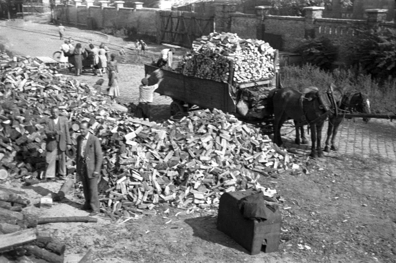 Budapest, 1948. augusztus Lovas kocsira pakolják a télire való tűzifát. A felvétel készítésének pontos dátuma ismeretlen. MTI Fotó/Magyar Fotó: Bartal Ferenc
