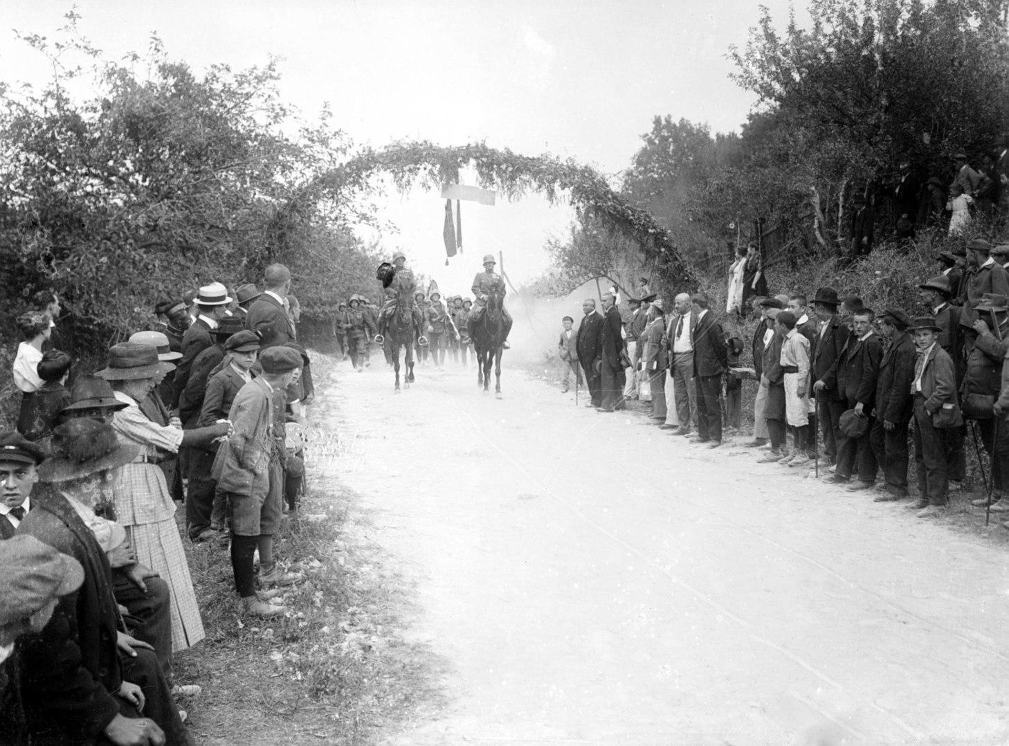 1914. június 28. Egy községben a lakosság ünnepi külsőségek között fogad egy harci felszerelésbe öltözött, rohamsisakos császári és királyi gyalogos alakulatot. A menet élén két tiszt lovagol.  MTI Fotó: Reprodukció