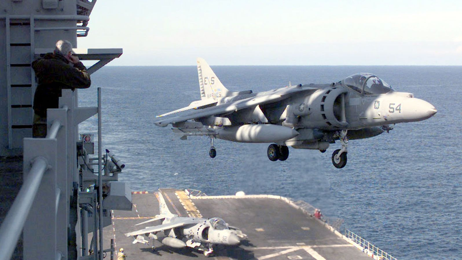"""The Air Boss Watches As The Last Av-8B """"Harrier"""" From Helicopter Medium Squadron Two Six Six Lands On Board USS Nassau April 14, 1999, Following A Strike Mission Into Kosovo. Embarked Aboard USS Nassau, Hmm-266 Launched The Amphibious Battle Group's First Strikes In Support Of Nato Operation Allied Force.  (Fotó: U.S. Navy/Getty Images)"""