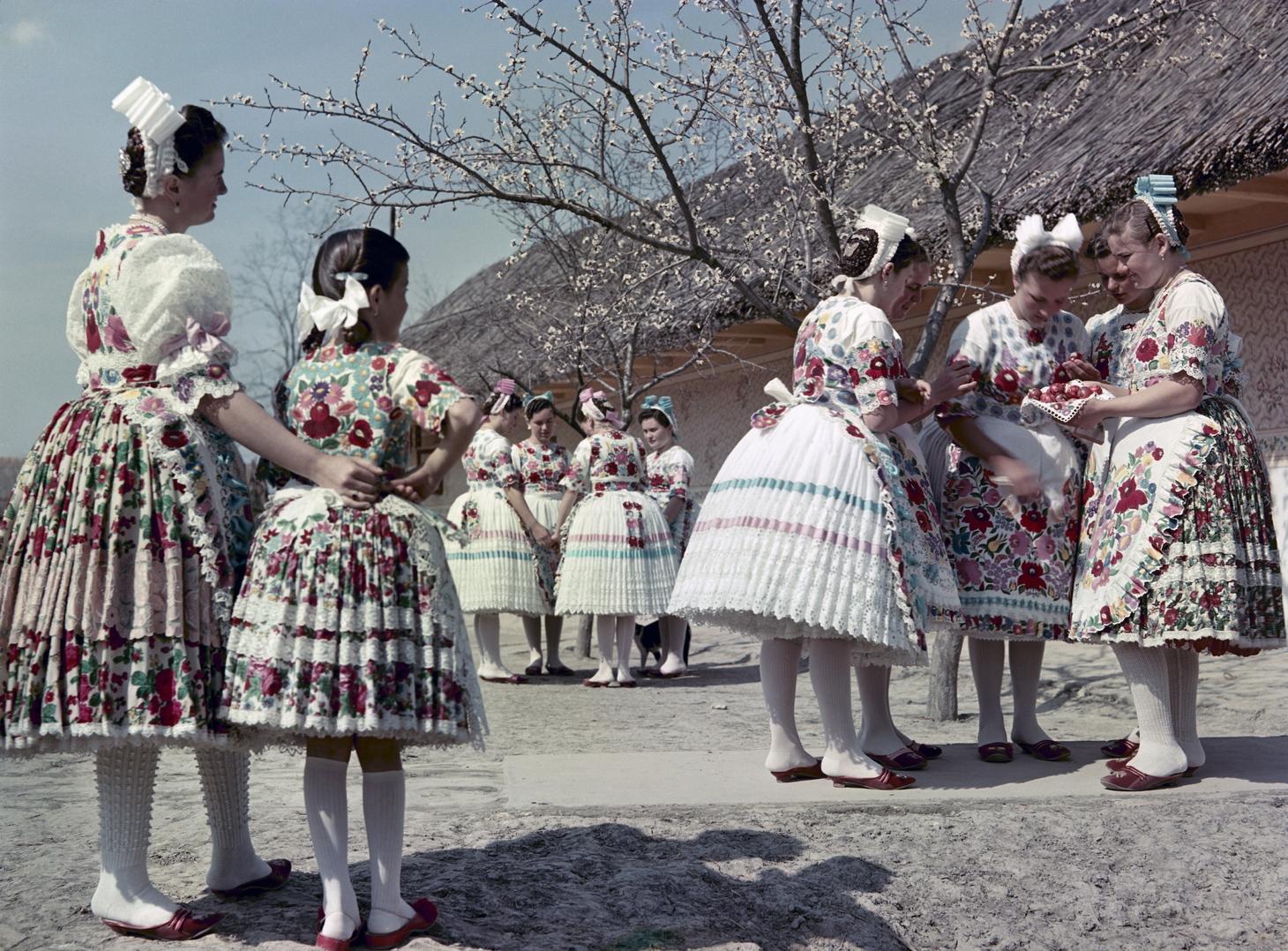 1959. április 2. Kalocsai népviseletbe öltözött fiatal lányok beszélgetnek és nézegetik a festett húsvéti tojásokat egy település utcáján.  A felvétel készítésének pontos helye ismeretlen. MTI Fotó: Járai Rudolf