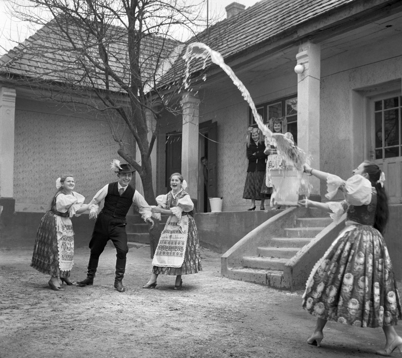 Őrhalom, 1961. március 31. Egy legényt fog le két lány Húsvét keddjén Őrhalmon, miközben társuk a település hagyományait követve meglocsolja egy vödör kútvízzel. MTI Fotó: Bajkor József