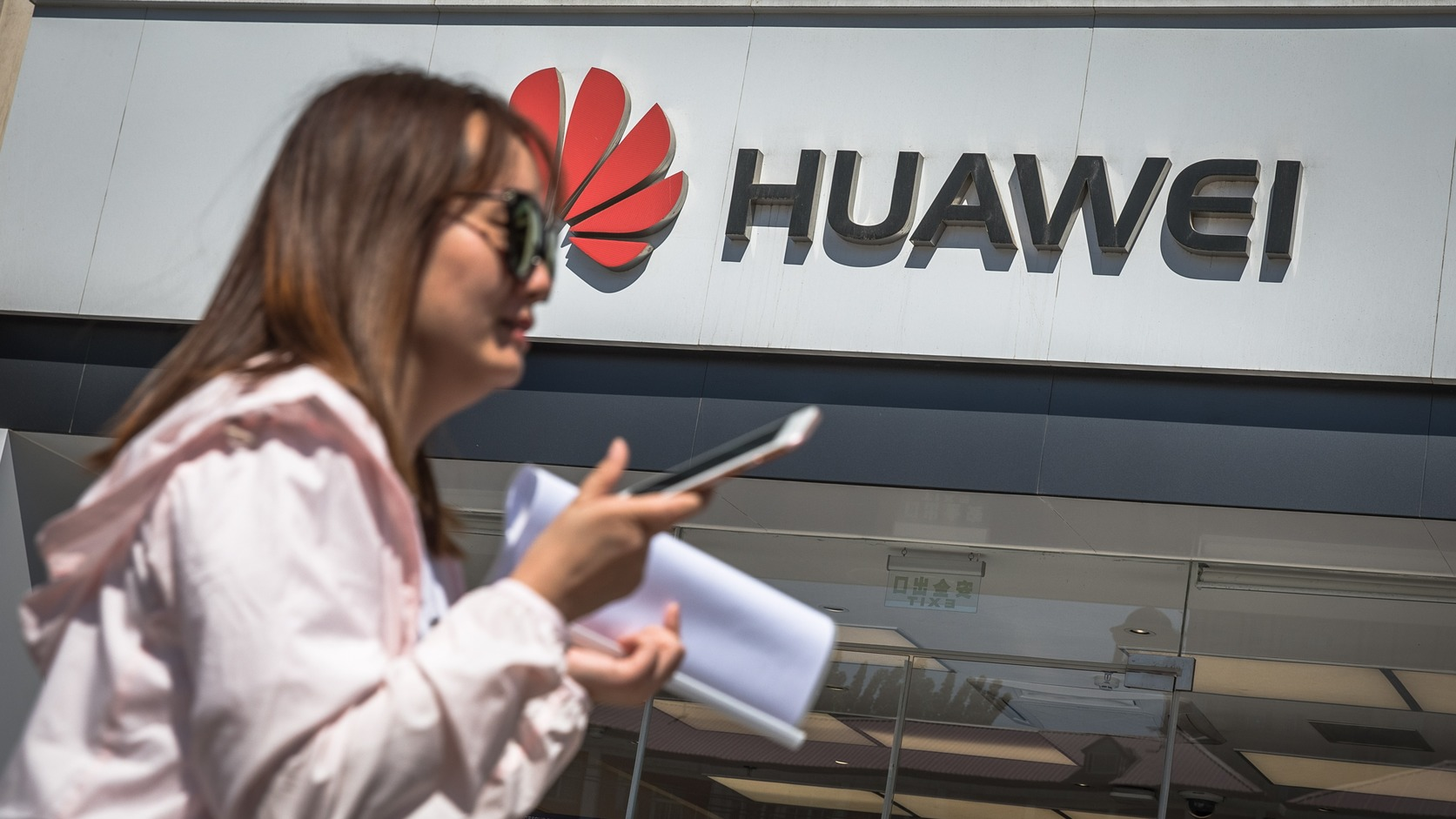 epa07586407 A woman walks past a Huawei store in Beijing, China, 20 May 2019. According to media reports on 20 May 2019, the US based multinational technology company Google halted business with Huawei in the wake of the Trump administration adding the Chinese telecommunication company to a trade blacklist over national security concerns. Huawei will lose access to updates for the Android operating system.  EPA/ROMAN PILIPEY