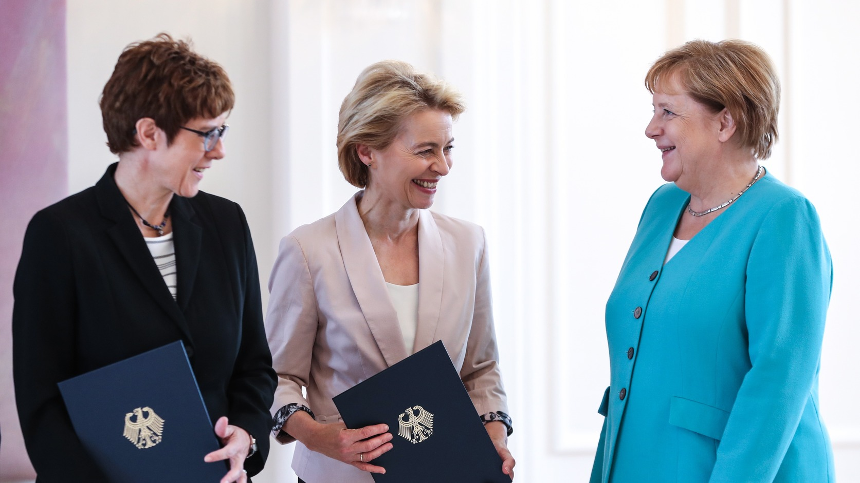 epa07721930 (L-R) Incoming German Defence Minister Annegret Kramp-Karrenbauer, outgoing German Minister of Defense Ursula von der Leyen, and German Chancellor Angela Merkel smile during the handing over of the certificate of discharge to von der Leyen and appointment to Kramp-Karrenbauer, at Bellevue Palace in Berlin, Germany, 17 July 2019. Mueller as First Vice President of the German Federal Council handed the certificates of discharge and appointment - signed by the German President Steinmeier - to the Ministry of Defense to outgoing von der Leyen and incoming Kramp-Karrenbauer.  EPA/FELIPE TRUEBA