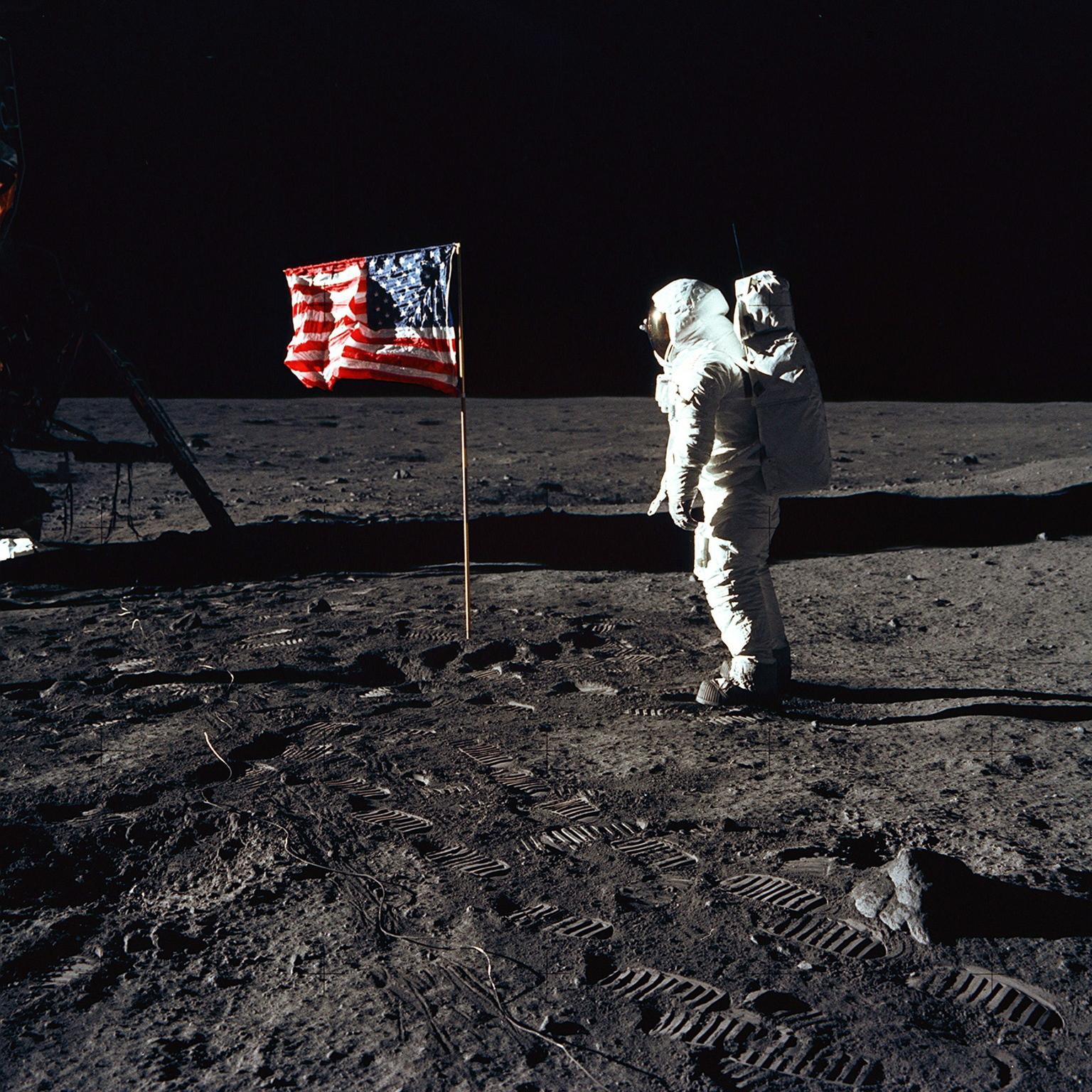 A NASA által közreadott képen Edwin E. (Buzz) Aldrin, az emberiség első holdutazását végrehajtó Apollo-11 amerikai űrhajó holdkompjának pilótája a Hold felszínén, a frissen kitűzött amerikai zászló mellett, a Nyugalom tengere nevű térségben az első Holdra szállás után, 1969. július 20-án. Balról a Sas leszállómodul egyik lába, a földön az űrhajósok lábnyomai láthatók. A felvételt a Holdra elsőként lépő Neil Armstrong amerikai űrhajós, az Apollo-11 parancsnoka készítette egy, az űrutazáshoz átalakított Hasselblad fényképezőgéppel, 70 mm-es gyújtótávolságú objektívvel. (MTI/NASA)