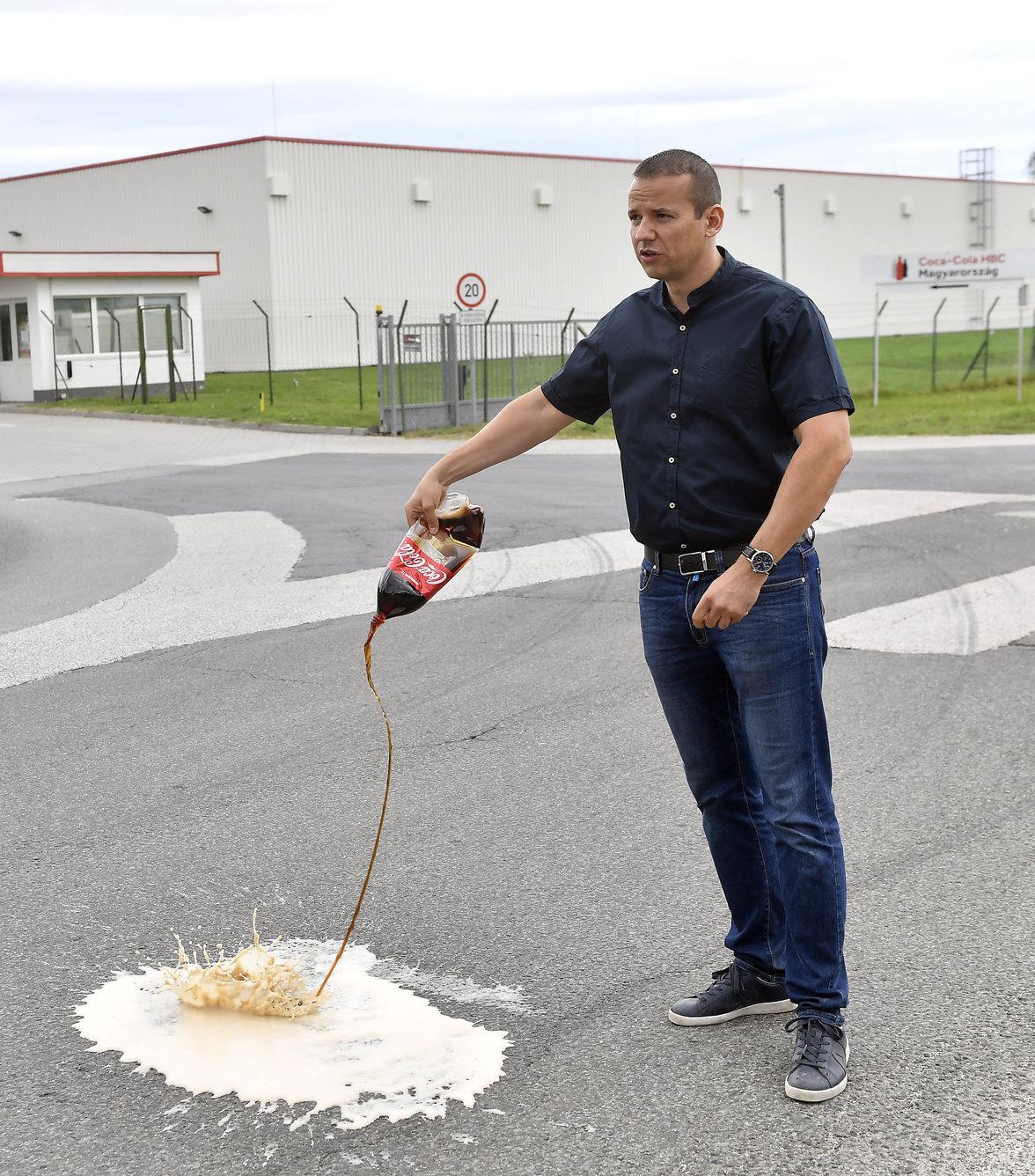 Toroczkai László, a Mi Hazánk Mozgalom elnöke tiltakozó akciójuk első lépéseként a Coca-Cola üdítőital-gyártó dunaharaszti telephelye előtti sajtótájékoztatóján az aszfaltra locsolja a támogatóik által felajánlott Coca-Cola terméket (Fotó: MTI/Illyés Tibor)